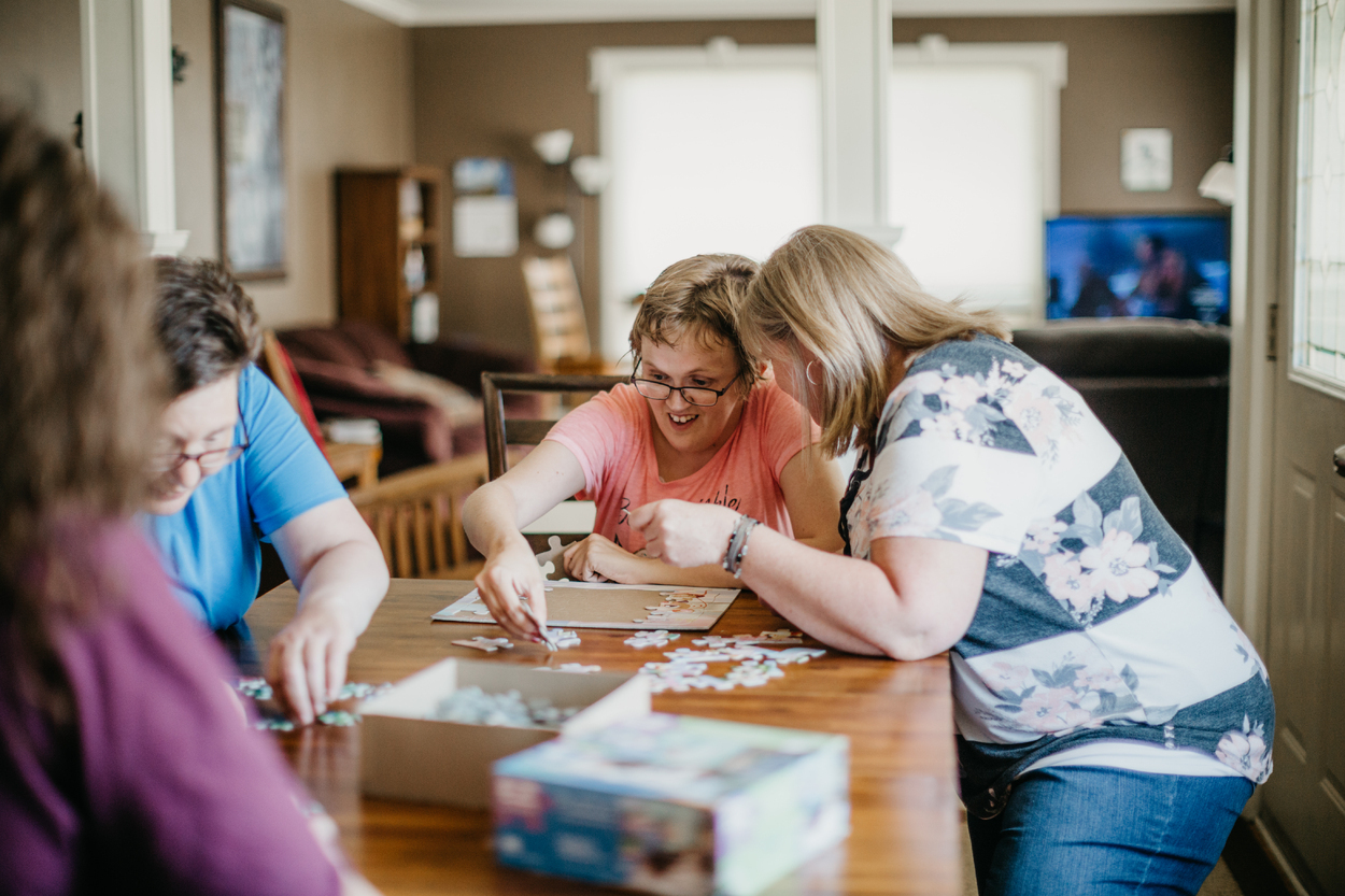 Community living services – women work together on a puzzle
